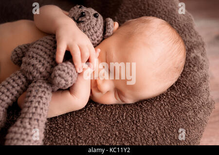 Newborn baby sleeping in a beautiful pose with a little bear - Stock Photo