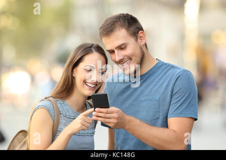 Happy couple searching on line content in a smart phone standing outdoors on the street - Stock Photo