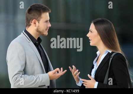 Side view portrait of two executives talking seriously standing outdoors on the street - Stock Photo
