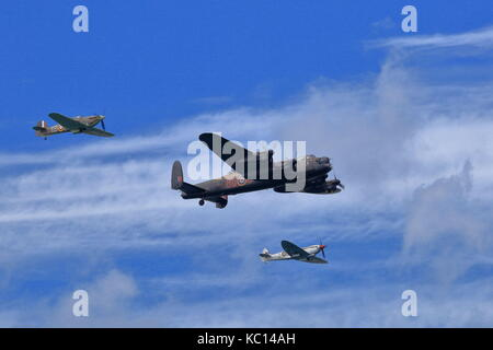Battle of Britain memorial flight with Lancaster Bomber flanked by a Hurricane to starboard and Spitfire to port - Stock Photo