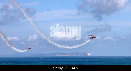 Breitling / Guinot Wingwalkers in 2009 livery swoop down at the Bournemouth Air Festival with Solent, Isle of Wight - Stock Photo