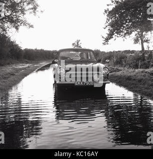 1960s, historical, father with young child in a Ford Cortina Mark 1 car on a flooded country lane. England, UK. - Stock Photo