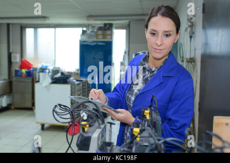 technician maintaining record of rack mounted server on clipboard - Stock Photo