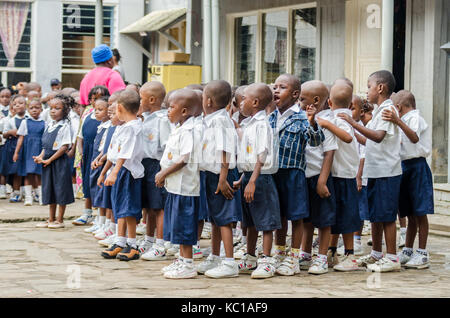 Group of young African pre school children dancing and singing in school courtyard, Matadi, Congo, Central Africa - Stock Photo