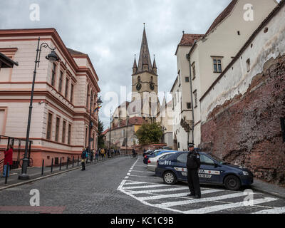 SIBIU, ROMANIA SEPTEMBER 22, 2017: Sibiu Local Police officer watching the Upper town of Sibiu, in Transylvania - Stock Photo