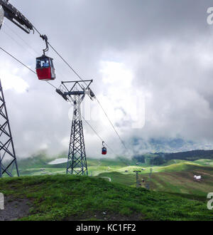 Red cable cabin down from Mannlichen with scenic view in direction to Grindelwald, Switzerland, Europe. - Stock Photo