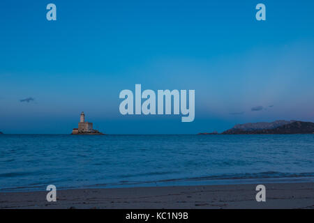 A view of lighthouse in Olbia gulf on sunset hour - Stock Photo