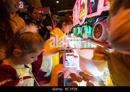 Young children playing penny arcade gambling machines in Blackpool Coral Island. Credit, LEE RAMSDEN / ALAMY - Stock Photo