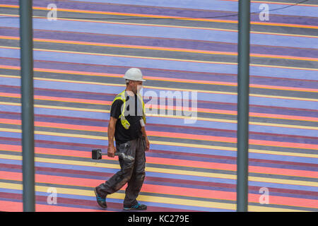 London, UK. 28th Sep, 2017. Workmen make final adjustments to the installation of the giant multicoloured carpet - Stock Photo
