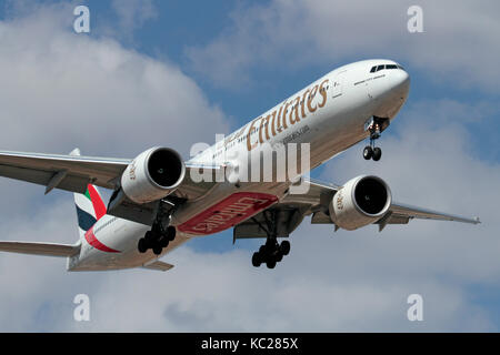 Long haul air travel. Emirates Boeing 777-300ER widebody passenger jet on approach - Stock Photo