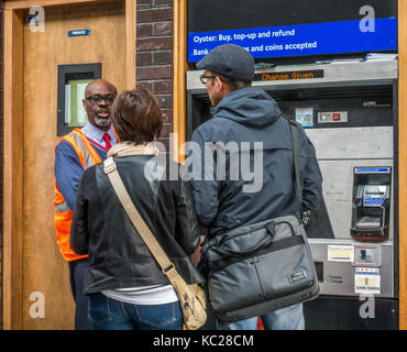 London Underground helpful assistant advising two people buying tickets at South Ealing tube station, London W5, - Stock Photo