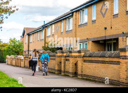 Two women with shopping - one using a walking stick - passing a row of modern terraced houses in South Ealing, London - Stock Photo