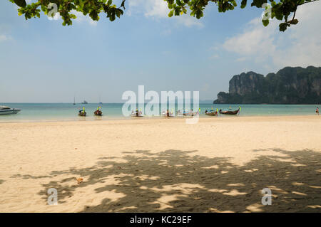 Long tail boats lined up along the shore on Krabi island, Thailand - Stock Photo