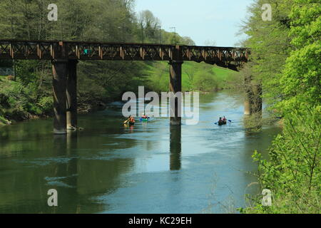 Railway bridge over the River Wye at Redbrook. A group of open canadian canoeist traveling underneath - Stock Photo
