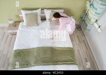 Young Female Housekeeper Arranging Bedsheet On Bed In Room - Stock Photo