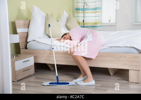Tired Young Female Housekeeper Lying On Bed In Hotel Room - Stock Photo
