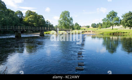 Footbridge and stepping stones across River Wharfe at Bolton Abbey, North Yorkshire - Stock Photo