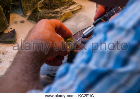 Master carver Gordon Wells carving a koru pendant from New Zealand jade (greenstone) at his former workshop in Hokitika. - Stock Photo