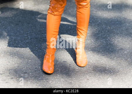 Milan, Italy - September 22, 2017: Model wearing a pair of orange high boots during the Armani parade, photographed - Stock Photo