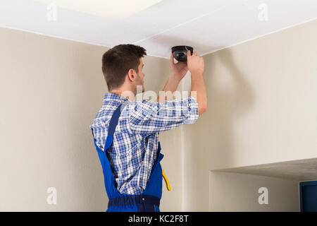 Male Technician Standing On Stepladder Fitting Cctv Camera - Stock Photo