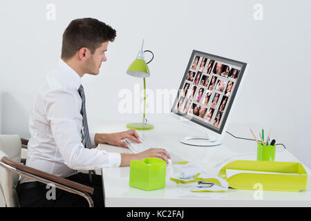 Young Businessman Editing Images On Computer In Office - Stock Photo