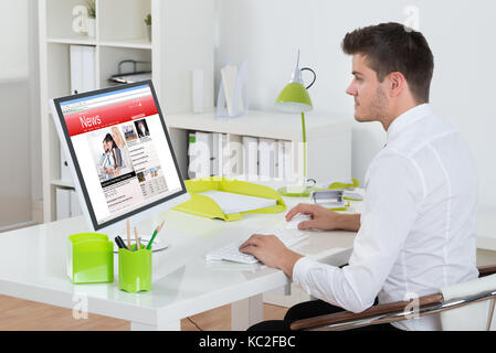 Young Businessman Watching Online News On Computer At Workplace - Stock Photo