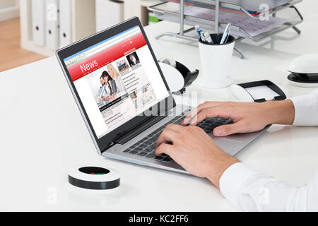Close-up Of Businessperson Checking Online News On Laptop At Desk - Stock Photo