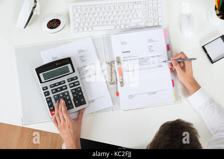 Close-up Of Businessperson Calculating Invoice With Calculator - Stock Photo