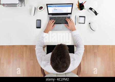 High Angle View Of Businessman Doing Login Of Online Account Using Laptop - Stock Photo