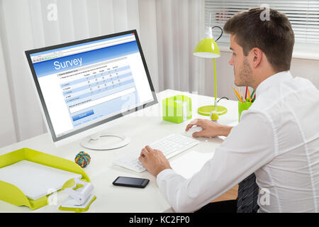 Young Businessman Filling Online Survey Form On Computer At Desk - Stock Photo