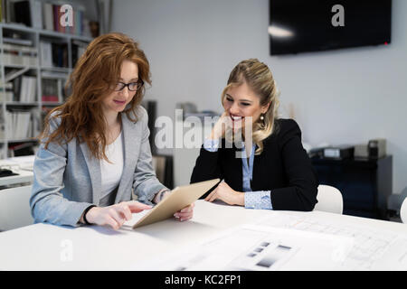 Young attractive architects using digital tablet in office - Stock Photo