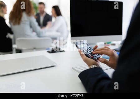Businessman analyzing investment charts with calculator on office desk - Stock Photo