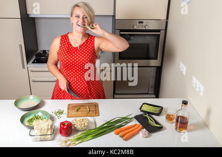 Girl biting asparagus and holding knife in other hand - Stock Photo