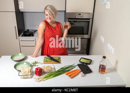 Adult girl holding whiskey glass in hand and smiling - Stock Photo