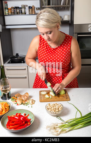 Cute girl cutting onions in red dotted dress - Stock Photo