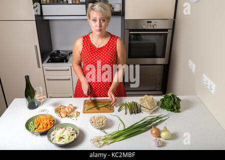 Surprised young woman in kitchen cutting asparagus - Stock Photo
