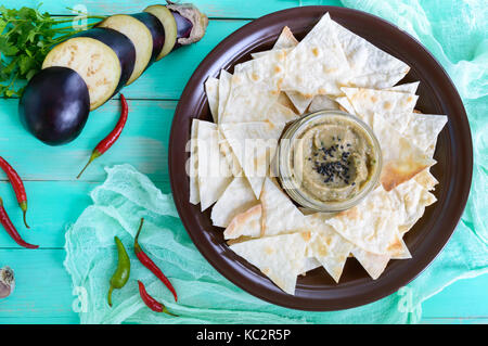 Light dietary pate from eggplant. Baba ganush is an Asian dish. Serve with thin lavash on a ceramic bowl. Top view. - Stock Photo