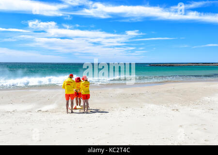 Three lifeguards standing on the beach at Mollymook, South Coast, New South Wales, NSW, Australia - Stock Photo
