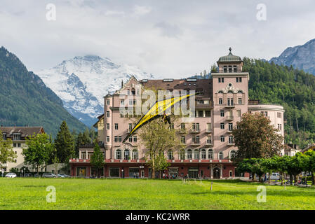 Interlaken, Switzerland - May 26, 2016: Tandem on the Hang Glider landing against the background of the Swiss Alps - Stock Photo