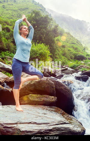 Woman in yoga asana Vrikshasana tree pose at waterfall outdoors - Stock Photo