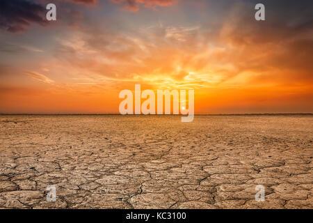 Cracked earth soil sunset landscape - Stock Photo