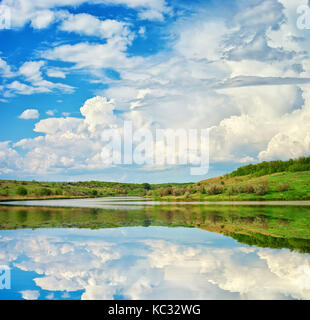 Lake and spring green hills. River in spring sunny day. Nature landscape composition - Stock Photo