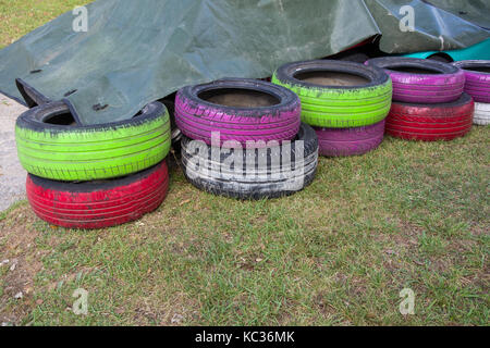 Colored used tires stoked in pile: painted in green, purple, white - Stock Photo