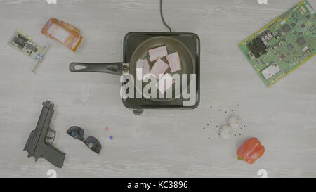 Man cooks meat in a frying pan. Man prepares the ham in the pan, on the table are: gun, glasses, chip and pepper, - Stock Photo