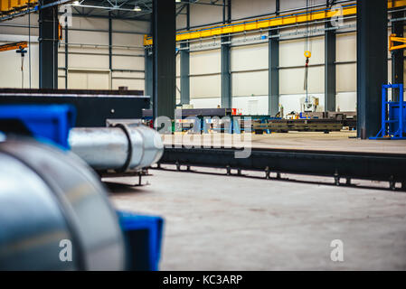 Metal Pipeline inside of big industrial hall - Stock Photo