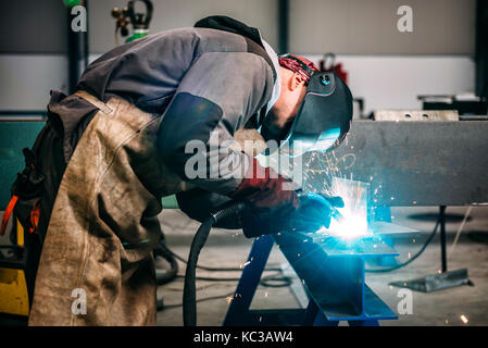 Industrial Welder With Torch and Protective Helmet in big hall welding metal profiles - Stock Photo