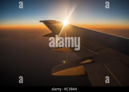 View of the sunrise and the clouds from within, out of the plane - Stock Photo