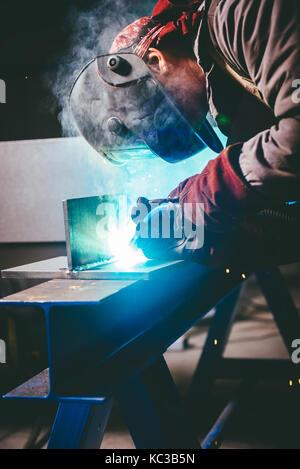 Industrial Welder With Torch and Protective Helmet in big hall welding metal profiles - Stock Photo