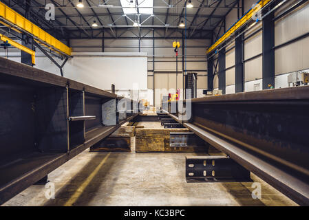 Metal profiles in big industrial hall with indoor crane in the background - Stock Photo
