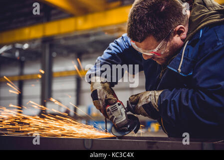 Worker Using Angle Grinder in Factory and throwing sparks - Stock Photo